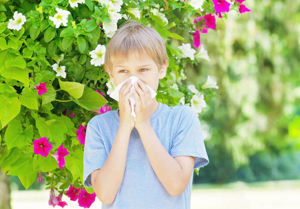 child sneezing near flowers