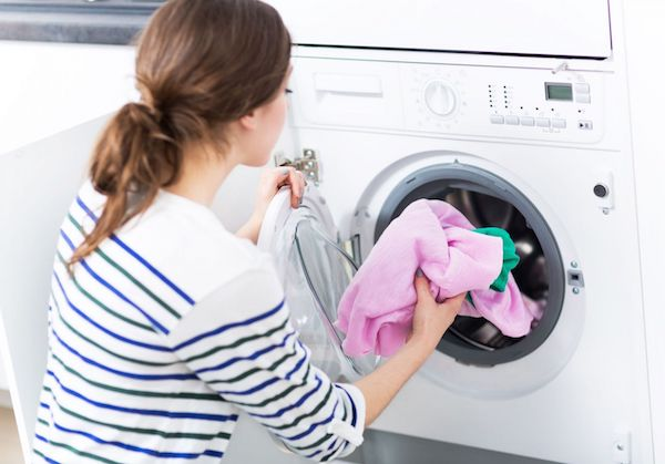 Woman putting laundry in washer
